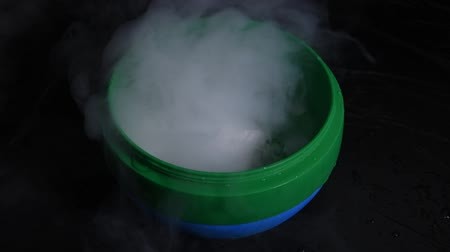 HD video white smoke movement in the green & blue bowl with effect of dry ice on darkness background
