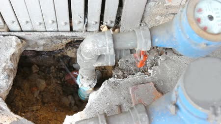 trubka : Water leaks from underground blue pipes.