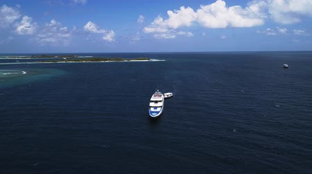 wide lens : Aerial view of the big yacht near the tropical island. Flying over the ocean. Stock Footage