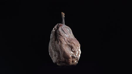 apodrecendo : Rotten moldy pear rotating on black background, isolated studio shot.