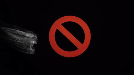 sem problemas : Crumpled used plastic bag moves through a stop sign on black background. Close-up loop video, stop motion animation, plastic pollution concept.