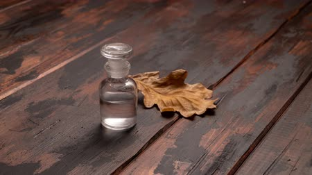 chene : Autumn cinemagraph. Small bottle and oak leaf on wooden background.