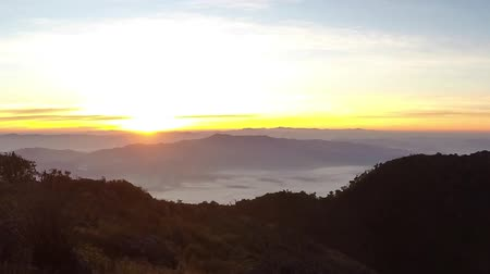 peak : Brilliant summit dawn above flowing cloud waves, red sun disk time lapse Stock Footage