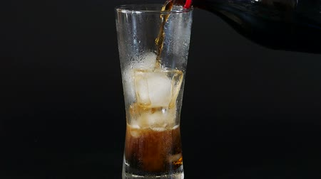kola : Pour the cola from a plastic bottle into a glass of ice over black background-food and drink concepts.