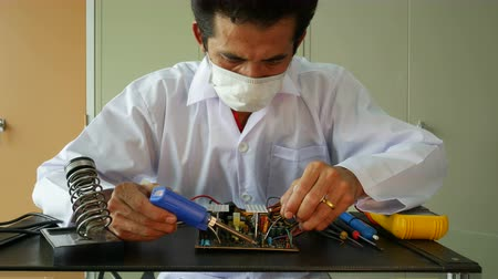 Electronics technician solder electronic circuit board. Stock Footage