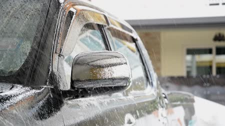 Sprinkle water on the car with a spray before cleaning the car with a car wash in the car care center.