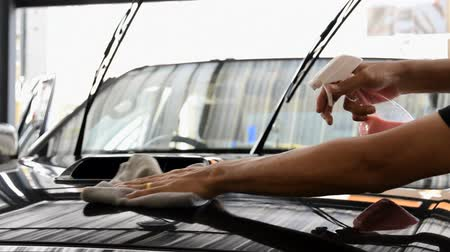 detailing : Cleaning staff is using a varnish and microfiber cloth to clean body of a car, concept for car care industry.