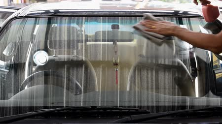 Cleaning staff is using a varnish and microfiber cloth to clean a glass of a car, concept for car care industry. Stock Footage