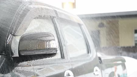 detersivo : Sprinkle water on the car with a spray before cleaning the car with a car wash in the car care center.