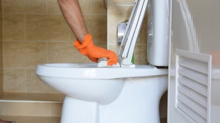 моющее средство : Hand of a man wearing orange rubber gloves is used to convert polishing to a toilet.