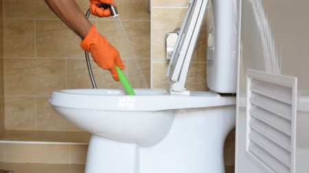 servant : Hand of a man wearing orange rubber gloves is used to convert polishing to a toilet.