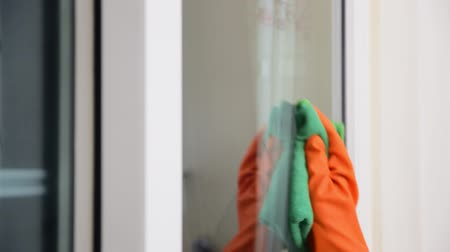 Womens hand wears orange rubber gloves, using green cloth to wipe the glass of the building with a glass cleaner.