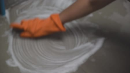 Womans hand wearing orange rubber gloves is used to convert scrub cleaning on the tile floor. Stock Footage