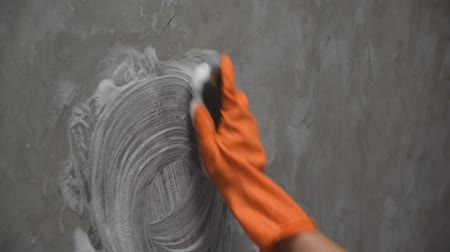 Womans hand wearing orange rubber gloves is used to convert scrub cleaning on the concrete wall.