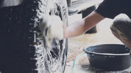 cera : Car wash staff are using a sponge moistened with soap and water to clean the wheels of the car.