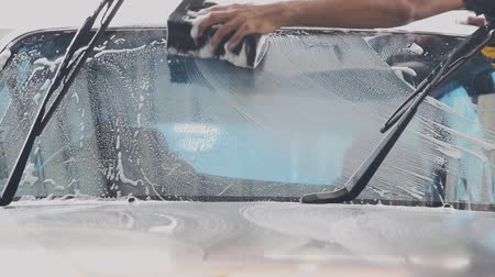 deterjan : Car wash staff is using a sponge to clean the windshield of the car.