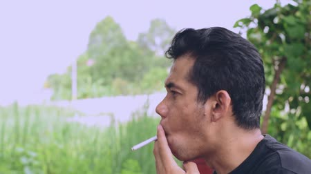 Asian men are standing smoking in the park, which is illegal in some countries.