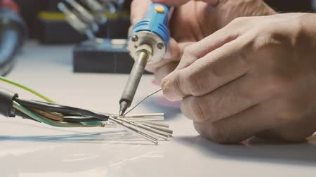 componentes : Electricians are using a soldering iron to connect the wires to the metal pin with soldering lead.