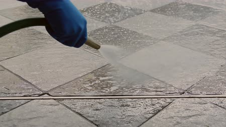 便利屋 : Hand of man wearing blue rubber gloves using a hose to cleaning the tile floor.