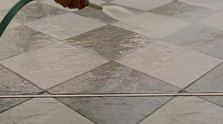Hand of man using a hose to cleaning the tile floor.