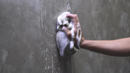 mold : Mens hands are using a sponge cleaning on the concrete wall.