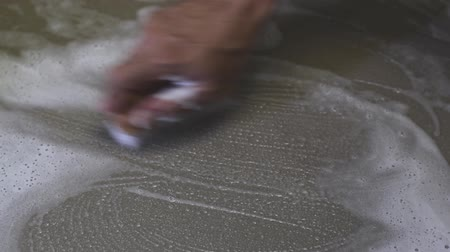 kielnia : Mens hands are used to convert polishing cleaning on the tile floor.