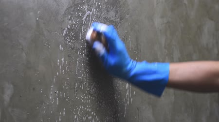 sıkıcı iş : Closeup hand wearing blue rubber gloves is used to convert scrub cleaning on the concrete wall. Stok Video