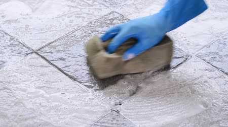 моющее средство : Hand of man wearing blue rubber gloves is using a sponge cleaning the tile floor.