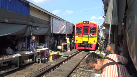 maeklong : SAMUT SONGKHRAM,THAILAND - APRIL 15 : A train is going through the Maeklong Market or Talat Rom Hup meaning the umbrella pulldown market on April 15, 2017 in Samut Songkhram,Thailand.