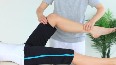 física : Woman doing some exercises helped by a physiotherapist
