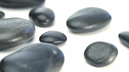 isolado no branco : Several black pebbles turning on a white background