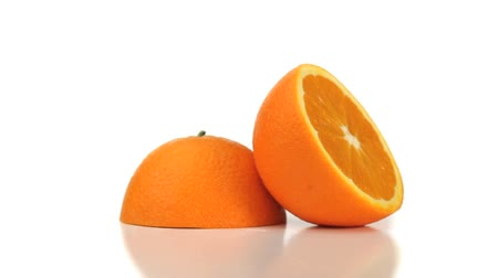 vitamin : Two halves of an orange turning on a white background