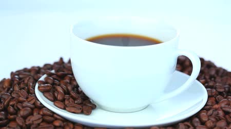 coffe : Cup of black coffee on a bed of coffee beans rotating on a white background