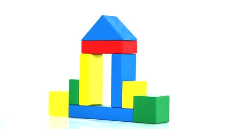 различный : Childrens coloured bricks forming a house on a white background Стоковые видеозаписи
