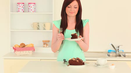 iştah : Beautiful brunette eating chocolate cake in the kitchen