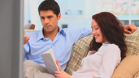 dívat se : Man watching tv while his girlfriend is reading a bookat home