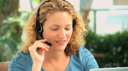 телемаркетинг : Curly blonde haired woman speaking over the headset in an office