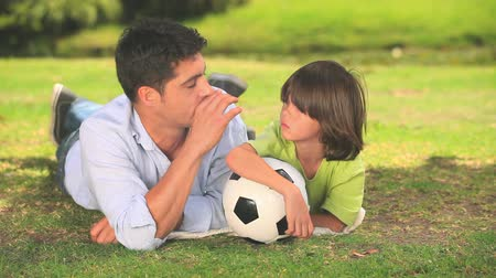 rekreasyon : A father and his son lying  talking on the grass while holding a football