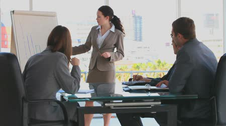 sala de reuniões : Business woman making a presentation in front of three business people