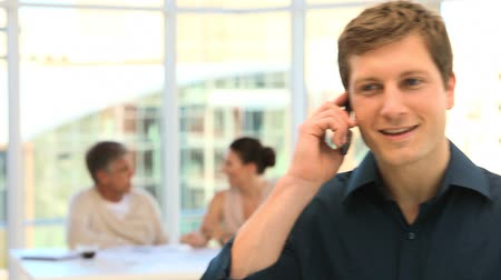 smartfon : Young man speaking on the phone with two business people in the background Wideo