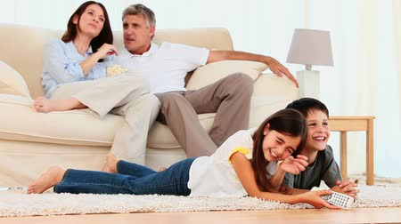 sitting room : Family laughing in front of tv in the living room Stock Footage