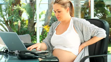 painéis : Tired pregnant woman having a back pain at her desk