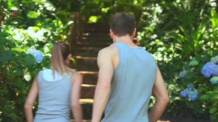 jogging : Couple running up a flight of steps  through a shrubbery Stock Footage