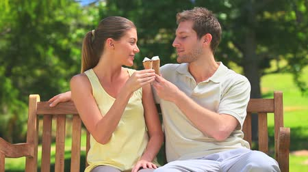 creams : Lovers eating ice creams on a bench in a beautiful park