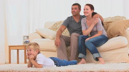 четыре человека : Lovely family watching the tv in the living room