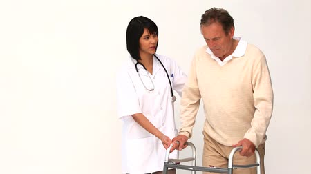 гражданин : A nurse helping her patient to use a walker isolated on a white background