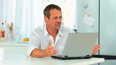 mężczyźni : Casual man laughing in front of his laptop in the kitchen