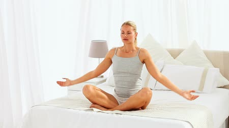 posição : Woman in lotus position sitting on her bed Vídeos