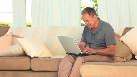 гостиная : Middle aged man using a laptop on his couch