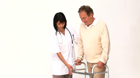 cidadão idoso : Nurse helping her patient to walk isolated on a white background Vídeos